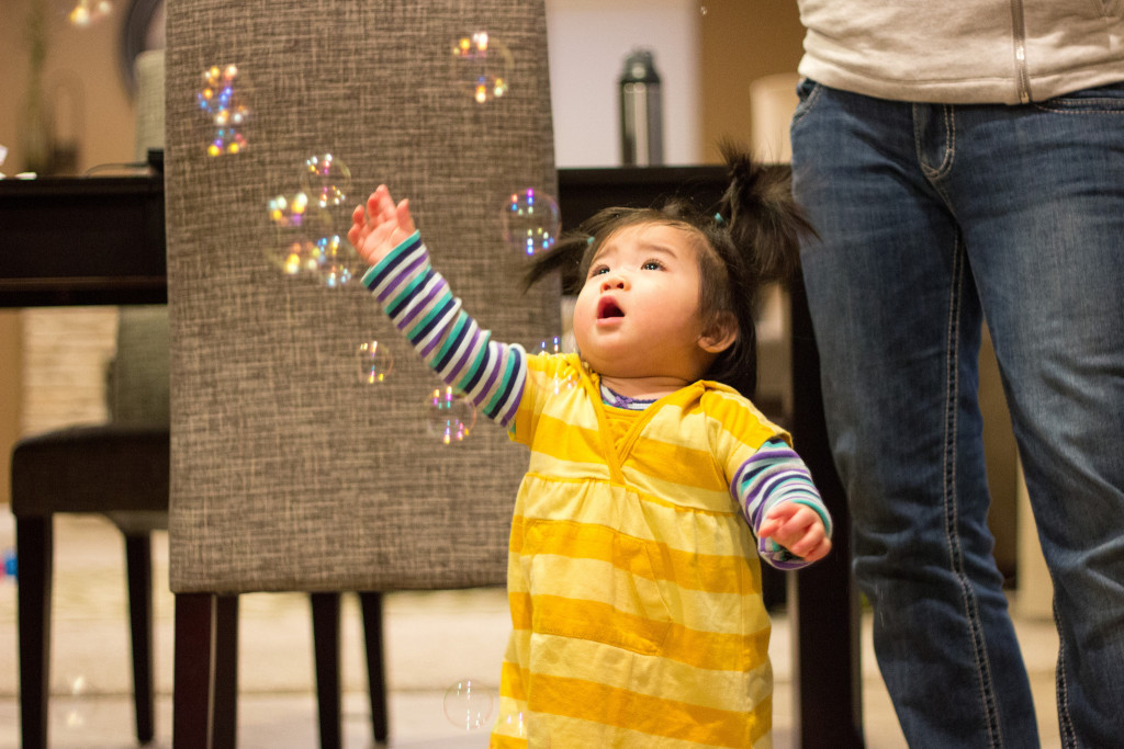 Playing with bubbles with Mommy while Daddy disapprovingly watches the bubbles get the floor wet!